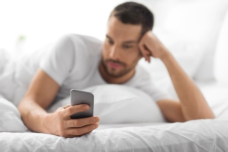technology, communication and people concept - close up of young man texting on smartphone in bed at home in morning