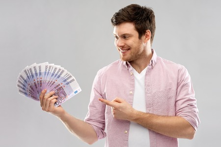 money, finance, business and people concept - smiling young man showing fan of five hundred euro bank notes over grey background
