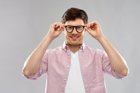 vision, education and people concept - smiling young man in glasses over grey background