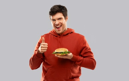 fast food, unhealthy eating and people concept - happy smiling young man in red hoodie with hamburger showing thumbs up over grey background Stock Photo
