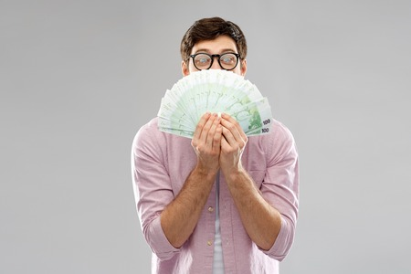 money, finance, business and people concept - happy young man in glasses with fan of one hundred euro bank notes over grey background Stock Photo