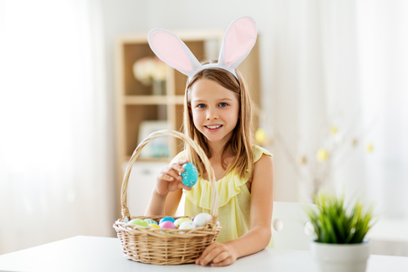 easter, holidays and people concept - happy girl wearing bunny ears headband with basket of colored eggs at home