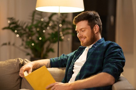 leisure, hygge and people concept - happy young man reading book at home in evening