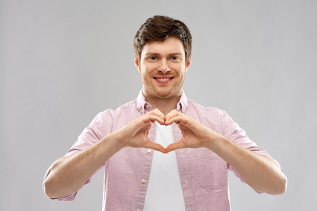 love, charity and valentines day concept - smiling man making hand heart gesture over grey background Stock Photo