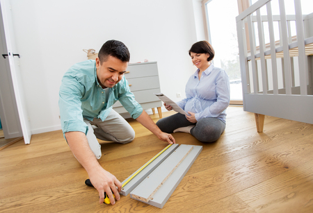 parenthood, family and nursery concept - happy middle-aged man and his pregnant wife user manual and ruler assembling and measuring baby bed details at home Stock Photo