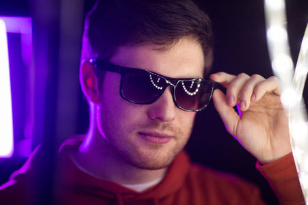 leisure, clubbing and nightlife concept - portrait of smiling young man in sunglasses at dark room over ultra violet neon lights of night club
