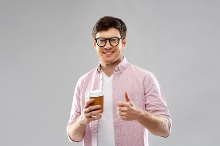 takeaway and people concept - young man or student in glasses drinking coffee and showing thumbs up over grey background