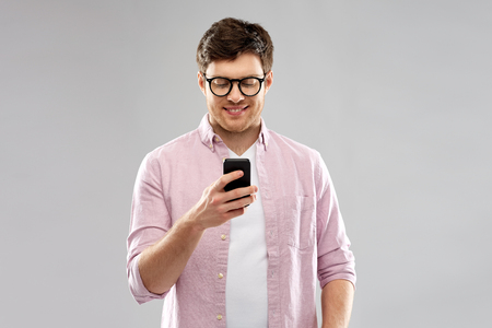 technology, internet and people concept - smiling young man in glasses looking at smartphone over grey background Stock Photo