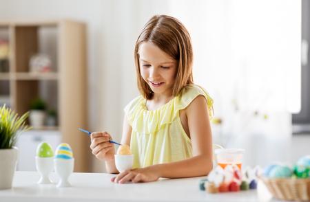 concept de pâques, de vacances et de personnes - une fille heureuse colorie des œufs avec des couleurs et un pinceau à la maison