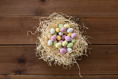 easter, confectionery and holidays concept - candy drop eggs in straw nest on wooden background Stock Photo