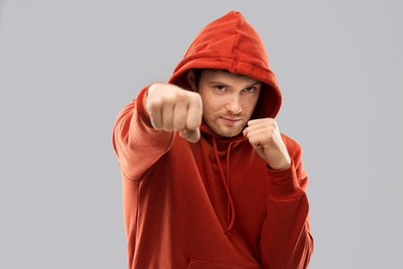 combat, aggression and people concept - young man in red hoodie fighting with fists or boxing over grey background Stock Photo