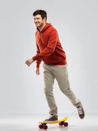 leisure, sport and people concept - happy smiling young man in hoodie riding on short skateboard over grey background
