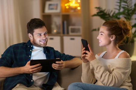leisure, technology and people concept - happy couple with tablet computer and smartphone at home in evening