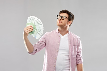 money, finance, business and people concept - proud young man in glasses with fan of one hundred euro bank notes over grey background 版權商用圖片