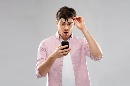 embarrassed young man looking at smartphone Banque d'images