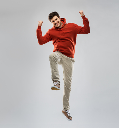 man in hoodie jumping and celebrating success