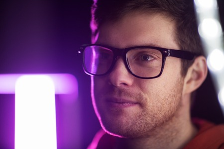 portrait of man in glasses over neon lights