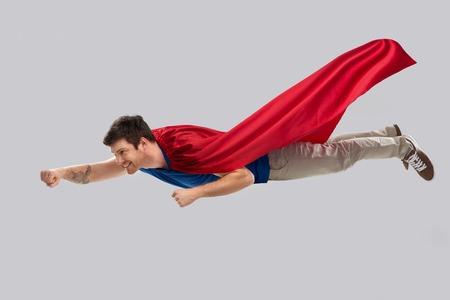 man in red superhero cape flying in air