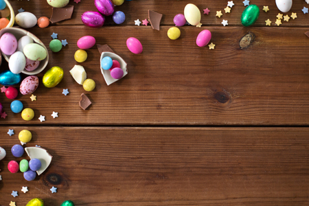 chocolate eggs and candy drops on wooden table Imagens - 119071047