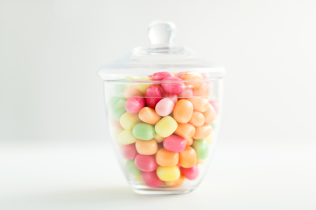 food, confectionery and sweets concept - glass jar with colorful candy drops over white background Фото со стока