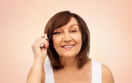 beauty, make up and old people concept - smiling senior woman applying mascara to eyelashes over beige background