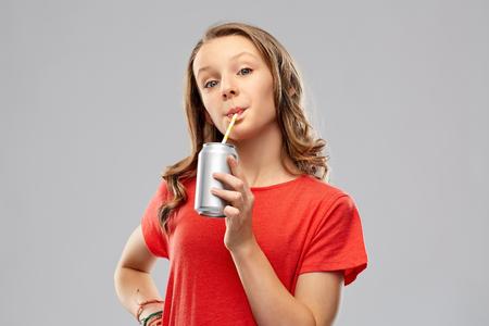 meisje drinkt frisdrank uit blik door papierstro Stockfoto