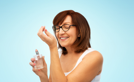senior woman smelling perfume from her wrist Imagens - 119009556