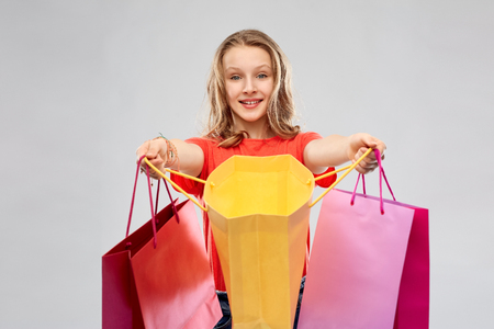 smiling teenage girl with shopping bags Imagens