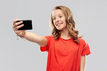smiling teenage girl taking selfie by smartphone
