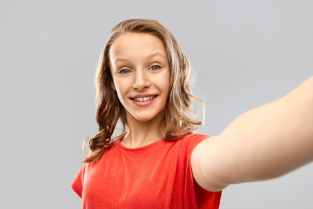 smiling teenage girl taking selfie Imagens - 119010713