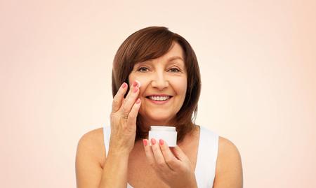 smiling senior woman applying cream to her face Imagens - 119010715