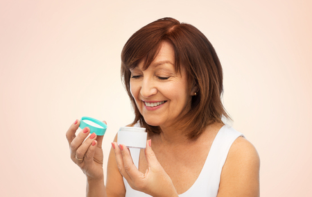 smiling senior woman with cream jar