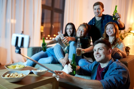 friendship, people, technology and party concept - happy friends with non-alcoholic drinks taking picture by selfie stick at home in evening Imagens - 119010927