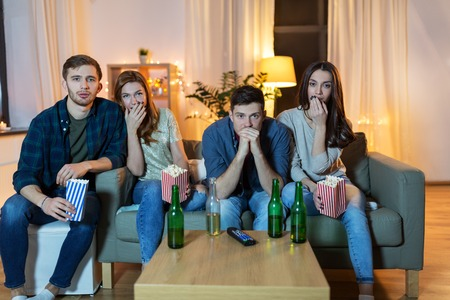 friends with beer and popcorn watching tv at home