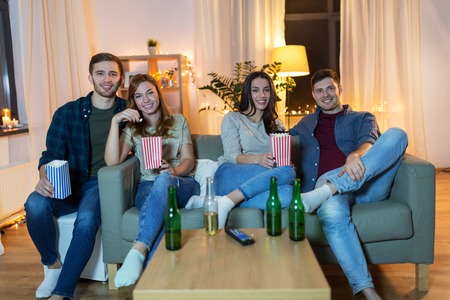 friends with beer and popcorn watching tv at home Imagens - 119010940