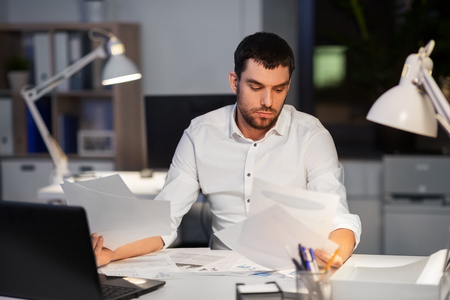 business, deadline and stress concept - businessman with papers working at night office Imagens - 119010947