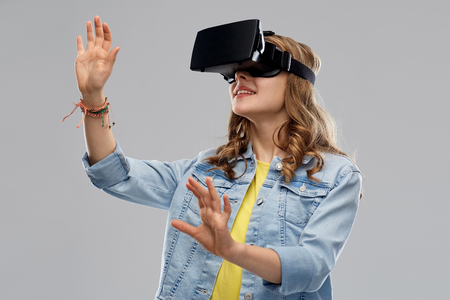 teen girl in virtual reality headset or vr glasses Stock Photo