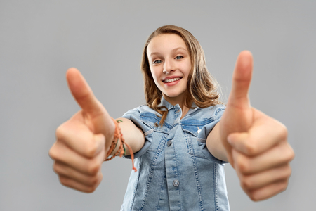 smiling teenage girl showing thumbs up Imagens - 119079320