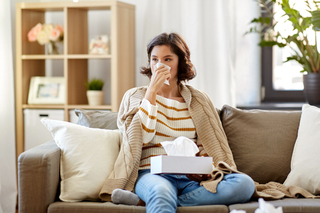 sick woman blowing nose in paper tissue at home Imagens - 119079323
