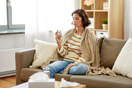 sad sick woman in blanket with drug at home Imagens - 119079471