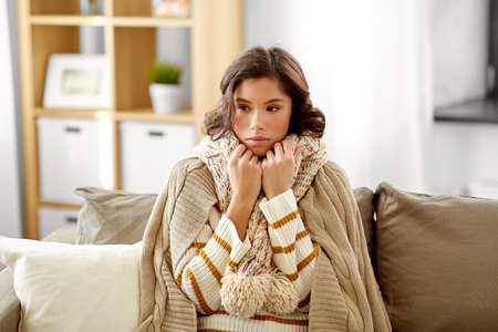 sad sick woman in blanket and scarf at home Imagens - 119079475