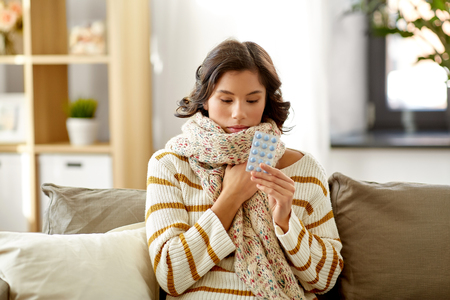 sick woman in scarf with medicine pills at home Imagens - 119079476