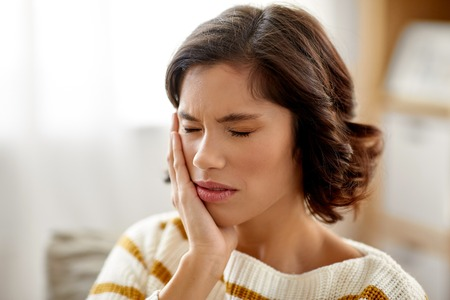 unhappy woman suffering from toothache at home Stockfoto