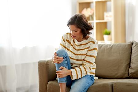 ongelukkige vrouw die thuis aan pijn in been lijdt