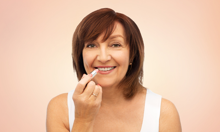 beauty, make up and old people concept - smiling senior woman applying lipstick to her lips over beige background