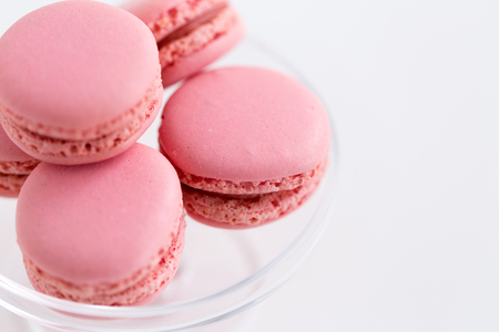 sweets, pastry and food concept - close up of pink macarons on glass confectionery stand over white background