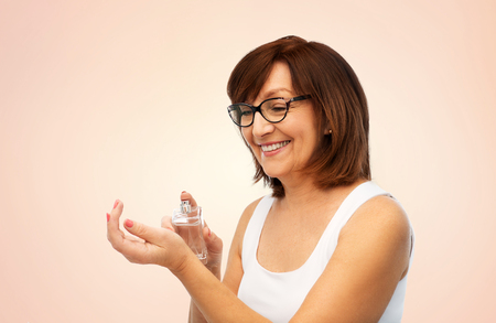 perfumery, beauty and luxury concept - happy smiling senior woman spraying perfume to her wrist over beige background Imagens - 119079489