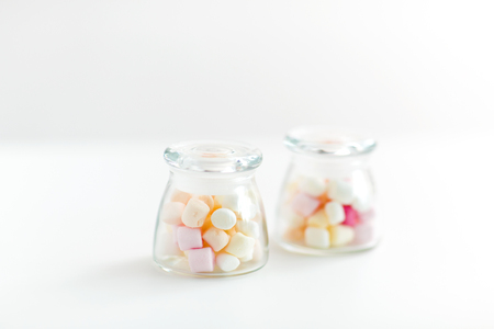 food, confection and sweets concept - close up of jars with marshmallows over white background Imagens - 119079521