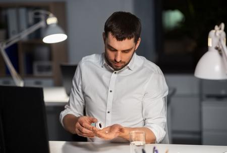 businessman taking medicine pills at night office Imagens - 119079526