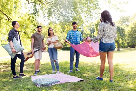 friends arranging place for picnic at summer park Imagens - 119079532